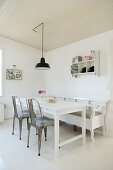 Metal chairs and bench around a wooden table in a white dining room