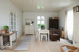 A Scandinavian-style dining room with ceiling panelling and wooden floorboards