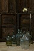 Wine jugs and a golden floor lamp in front of an old wooden door