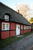 Red half-timbered house with thatched roof on the gravel path in autumn