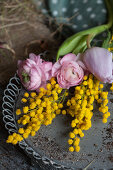 Ranunculus, tulips and mimosa flowers on metal tray