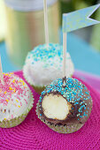 Cake pops decorated with sprinkles and paper flags