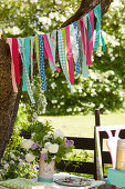 Garland handmade from colourful strips of fabric in garden