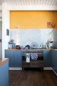Blue-grey base units and yellow wall in kitchen-dining room