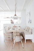 Solid wooden dining table with various chairs and bench in open-plan dining area