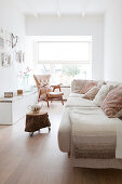 Pale sofa with scatter cushions, low sideboard and retro armchair in living room