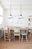 Solid wooden dining table with various chairs below vintage pendant lamps