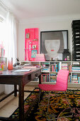 Pink chair on the old wooden table in front of the half-height shelf in the study