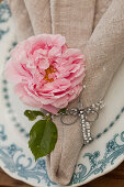 Rose and dragonfly made from wire and beads on linen napkin