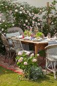 Festively set table on rug in summery garden