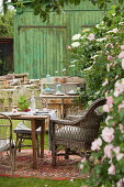 Table and chairs on rug on lawn in summery garden
