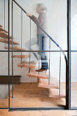 Woman walking up staircase behind glass wall