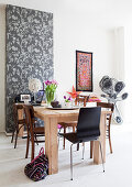 Solid wood table with various chairs in front of wallpaper with a floral pattern