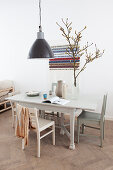 Black pendant lamp above dining table with chairs, branch in vase, behind it wall hanging with message
