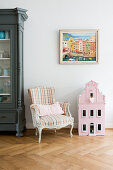 Baroque chair, painting of Mediterranean town and dolls' house on herringbone parquet floor