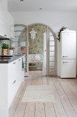 Retro fridge, wooden floor and arched lattice door in white kitchen
