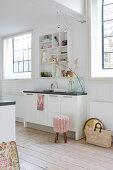 Narrow kitchen counter between two lattice windows in white kitchen