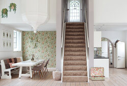 Staircase between dining room and kitchen in open-plan interior