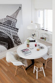 Round table with shell chairs and stools next to large photo of Eiffel tower