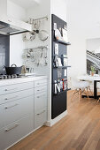Pale grey kitchen counter with extractor hood and kitchen utensils hung from rods