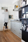 Woman opening white, floor-to-ceiling cupboards in kitchen