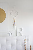 White bed headboard below decorative letters and dreamcatcher on wall