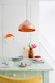 Green-painted kitchen table below copper pendant lamp