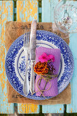 Napkin decorated with French marigold, phlox and verbena flowers on old plate