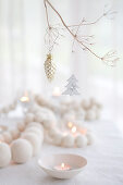 White wooden bead necklace and tealights on table and Christmas decorations hung from branch