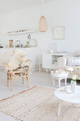 Rattan chair with sheepskin rug, tables and sideboard in white living room