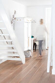 White wooden stairs and festively decorated white cupboard in hallway