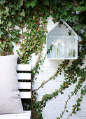 Shelf in the shape of a house on a brick wall covered with ivy