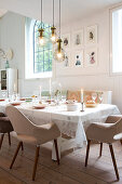 Festively set table with upholstered retro chairs