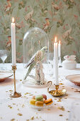 Bird figurine and bead necklace under glass cover on table festively set with candles, macarons and gold stars