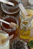 Different types of honey in glasses with wooden craft sticks and honey dipper