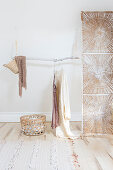 Hanging branch on wooden bead chains as a clothes rail next to a screen