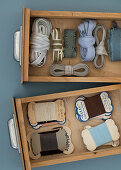 Fabric ribbons and old sewing thread in wooden drawers
