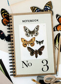 Postcard with butterfly motifs and number 3 on a notebook