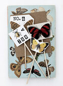 Homemade plant plugs with a butterfly motif, beetles, and numbers