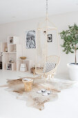 Hanging chair and side table on cowhide, shelf modules in the background