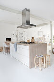 Kitchen island, ceiling-mounted hood in open plan living space