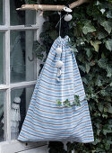 A homemade sack made of striped fabric hanging from the window