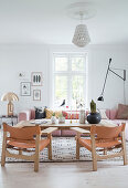 Pink upholstered sectional sofa, golden table lamp, rustic coffee table, and leather chairs in the living room