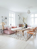 Pink upholstered suite, golden table lamp, rustic coffee table and leather chairs in the living room