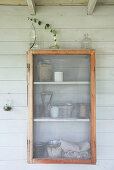 A wall cupboard with a fly screen and cuttings in glass containers