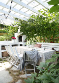 Dining table with chairs and bench and green plants on covered terrace