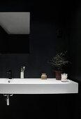 A white washbasin against a black wall in a bathroom