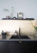 A dark kitchenette with a sink