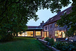 View from garden into the kitchen at dusk with original brick and flint farmhouse