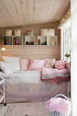 A cosy day bed in a small room with panelled walls and ceiling